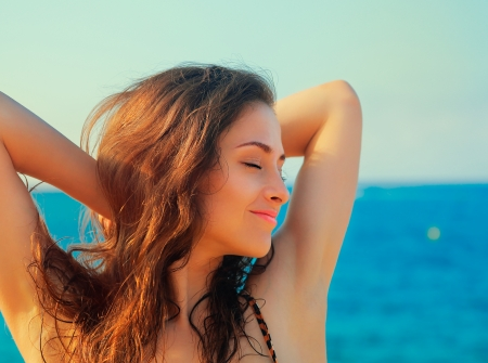 Beautiful happy woman joying with closed eyes on blue sea and sky background  Closeup portrait Stock Photo