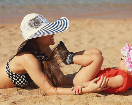 Happy mother and kid playing on beach sand near sea  Closeup portrait photo