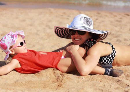 Happy mother and kid lying on the sand on beach in hat and glasses photo