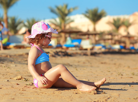 Kid ni�a sentada en la playa de arena y tomar el sol photo