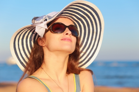 Beautiful woman in hat and sun glasses looking up and joy on blue sea background  Closeup portrait photo