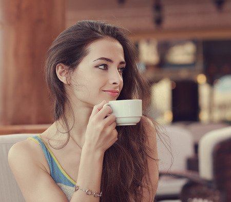 Beautiful smiling woman drinking coffee from cup and looking photo
