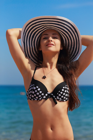 Sexy bikini woman in hat looking happy on blue sea background photo