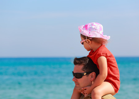 Father and kid girl sitting on shoulders on blue sea background photo