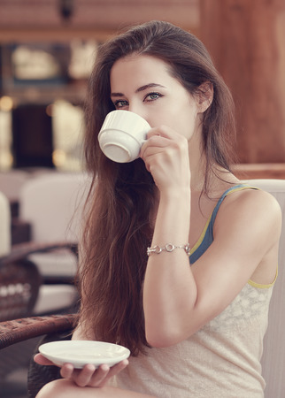 Beautiful thinking girl drinking coffee  Closeup vintage portrait photo