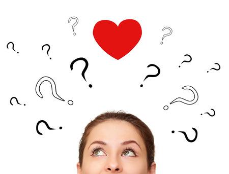 Belle fille réflexion sur l'amour avec beaucoup de questions et le coeur au-dessus de la tête isolé sur blanc