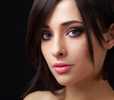 Beau visage de femme de maquillage parfait avec de longs cils sur fond noir