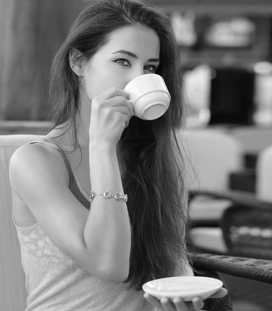 Beautiful thinking girl drinking coffee in cafe  Black and white portrait