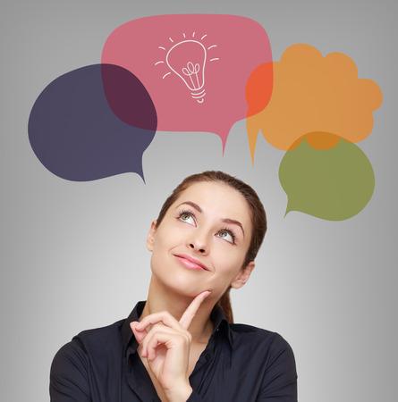 ビジネスの女性と灰色の背景にバブルのアイデア電球を考えてください。