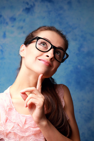 Thinking happy girl in glasses looking up on blue background Stock Photo - 26655319