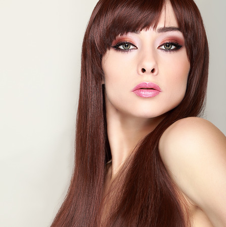 Fashionable female model with long hair and bright makeup looking sexy photo