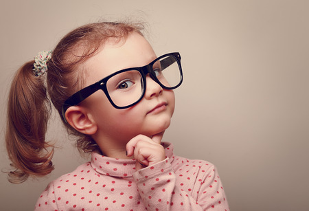 glasses eye: Thinking kid girl in glasses looking happy  Closeup instagram effect portrait