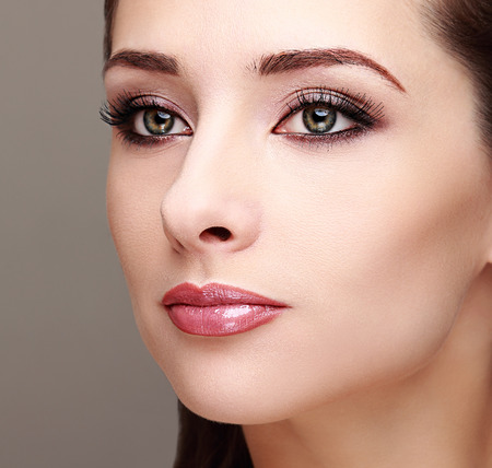 Beautiful perfect makeup woman face  Long lashes and smoky green make eyes  Closeup photo