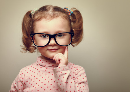 Thinking little kid girl looking happy in glasses  Vintage portrait Stock Photo