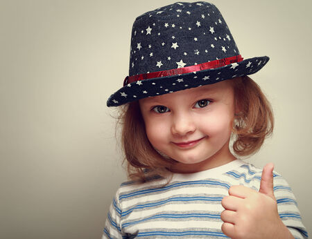 Smiling kid girl in blue hat showing thumb up sign  Closeup photo