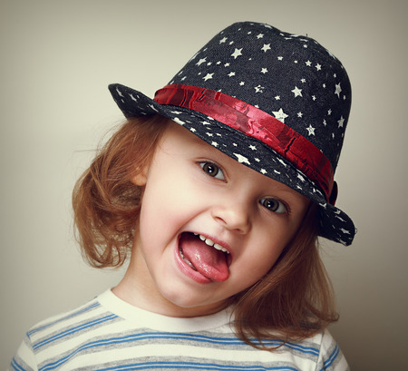 Happy showing the tongue kid girl in fashion hat  Closeup vintage portrait photo