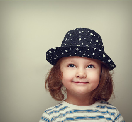 vintagel: Dreaming smiling beautiful girl in hat looking up on empty space Stock Photo