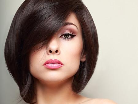 Belle femme de maquillage lumineux avec le noir Gros plan de style de cheveux courts