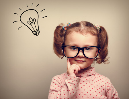 Thinking happy kid in glasses with idea bulb above the head Stock Photo