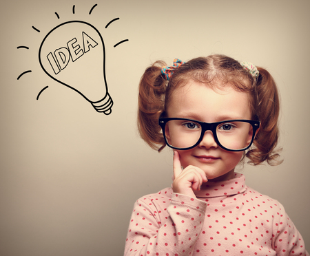 Cute thinking kid girl in glasses with idea bulb looking photo