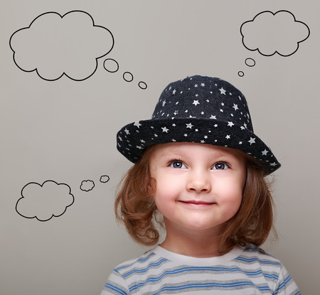 Thinking cute kid girl with many ideas in empty bubble