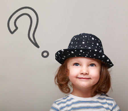 Thinking cute kid with big question sign above looking up on grey background
