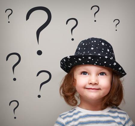 Pensée Fille heureuse d'enfant dans le chapeau regardant sur de nombreuses questions-dessus de la tête