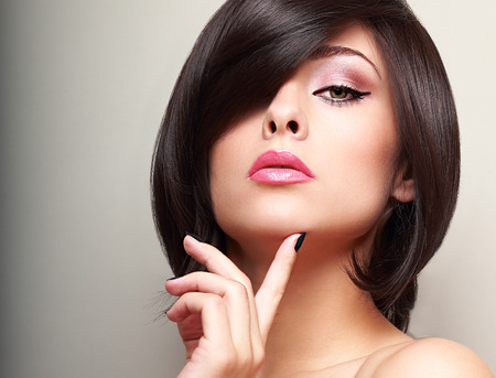Sexy black short hair style female model looking with finger near the face  Beautiful bright makeup photo