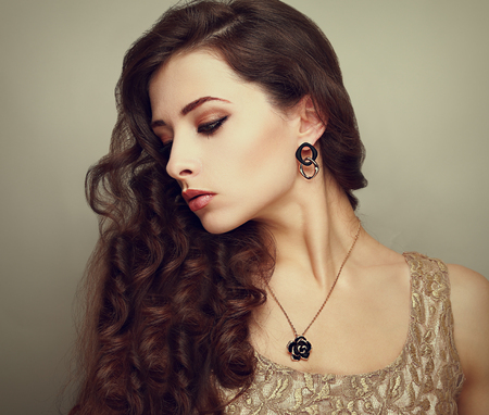 Beautiful profile of female model looking down with long brown curly hair  Vintage portrait photo