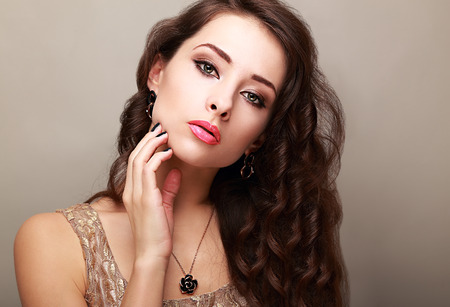 Beautiful bright makeup woman with long hair touching the face photo