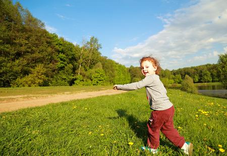 Running happy kid girl outdoors bright summer background Stock Photo - 28450093