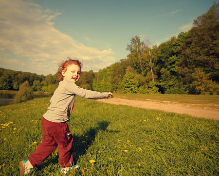 Happy smiling kid girl running on green grass outdoors summer background in bright sunny day Stock Photo - 28450095