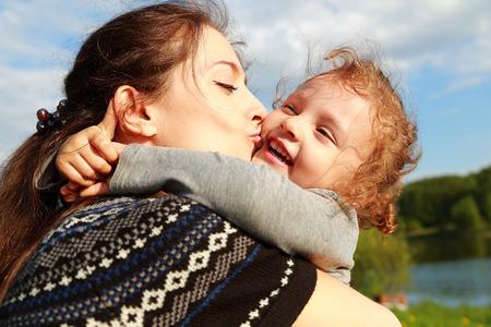 Belle mère embrassant heureux rire enfant fille à l'extérieur de fond en été