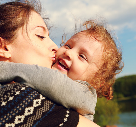 Mother kissing happy child outdoors summer background  Closeup portrait photo