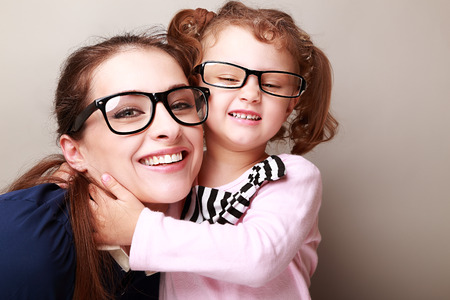 daughter: Happy young mother and lauging kid in fashion glasses hugging