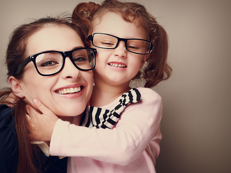 Loving happy mother and smiling daughter hugging  Vintage closeup portrait photo