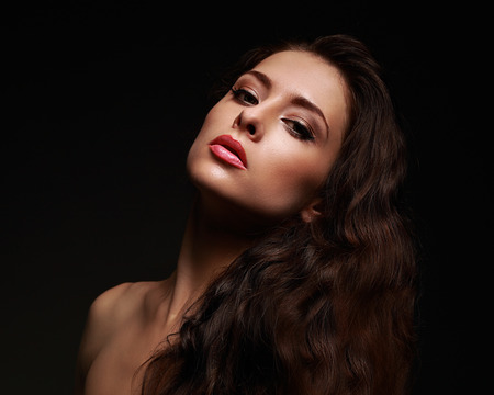 Beautiful makeup woman with long curly hair on black background photo