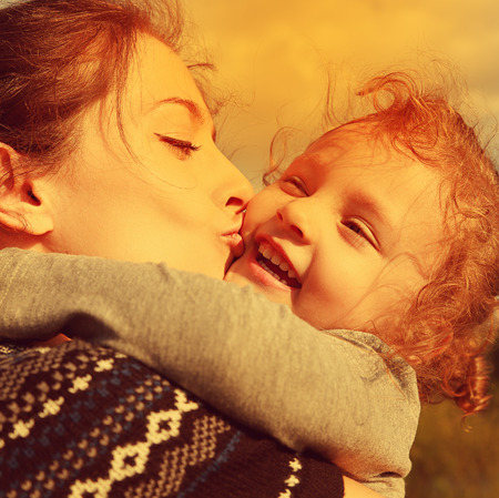 Bright closeup portrait of happy mother kissing laughing daughter  photo