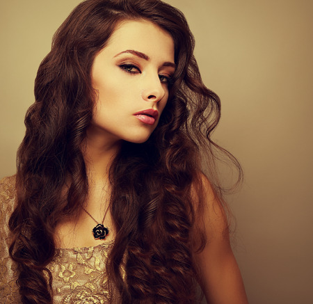 Beautiful bright makeup woman with long curly hair looking sexy photo