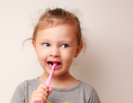 Funny kid girl brushing the teeth and looking photo