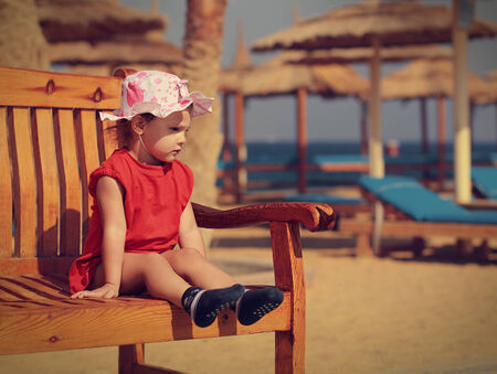 Small cute kid girl sitting on the bench on beach background and looking serious photo