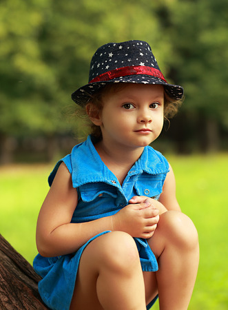 Cute kid in fashion hat sitting on green park summer background photo