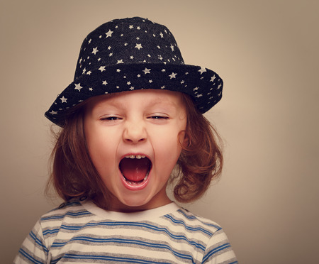Angry shouting kid girl with open mouth  Closeup vintage portrait photo