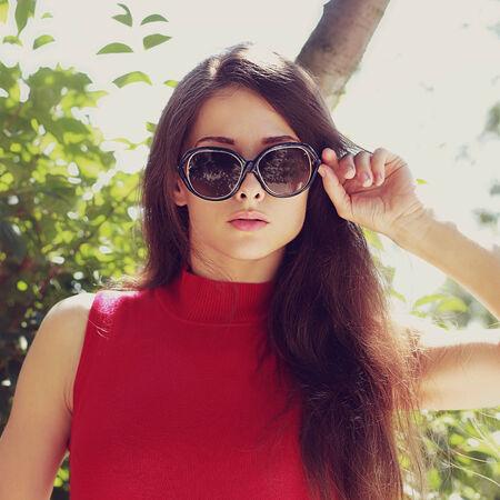 Female model in sunglasses looking outdoors  Closeup portrait photo