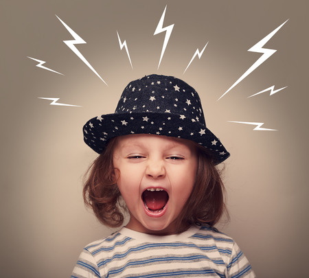 Angry kid in hat screaming with open mouth and white lightnings above on dark background photo