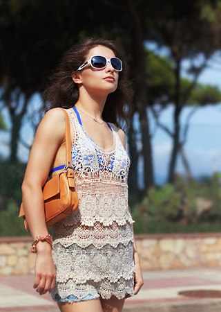 Beautiful urban woman in beach dress and sunglasses with leather bag on shoulder on the street background photo