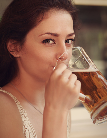 Happy woman drinking beer from big glass. Vintage portrait photo