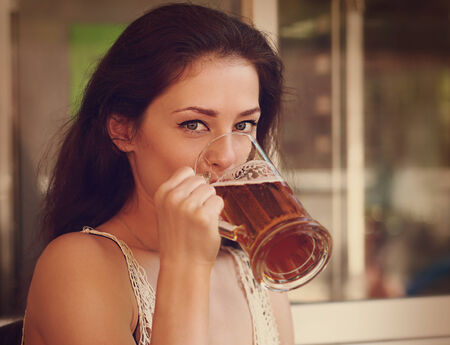 Happy woman drinking light lager beer in pab ang looking. Vintage portrait photo