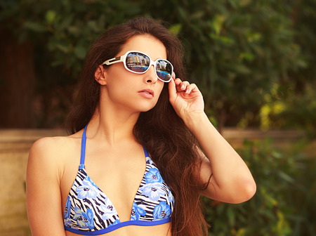 Beautiful bikini woman in fashion sunglasses looking sexy outdoor background photo