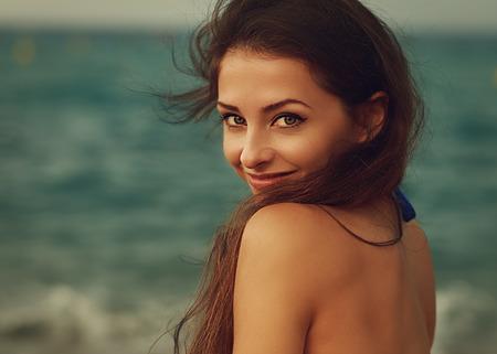 Sourire jeune femme air heureux sur mer fond. Gros plan portrait cru Banque d'images